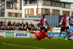 April 9 2016 - Kingfield Stadium - Woking - England - Woking Defender Cameron Norman (26) is stopped by some last ditch defending by Gateshead striker Ryan Bowman and Gateshead goalkeeper Sam Russell during the National League match between Woking & Gateshead.