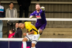 April 30 2016 - Kingfield Stadium - Woking - England - Woking Goalkeeper Jake Cole (1) jumps with Eastleigh Striker Ross Lafayette (11) to punch clear during the National League match between Woking & Eastleigh.