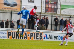 March 5 2016 - Kingfield Stadium - Woking - England - Woking's Carr jumps with Dover Defender Richard Orlu (6) during the National League match between Woking & Dover Athletic.