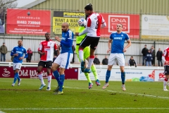 March 5 2016 - Kingfield Stadium - Woking - England - Woking Midfielder Keiran Murtagh (8) challenges Dover Goalkeeper Mitchell Walker (1) for a cross during the National League match between Woking & Dover Athletic.