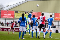 March 5 2016 - Kingfield Stadium - Woking - England - Dover Goalkeeper Mitchell Walker (1) jumps through the crowd to clear a woking cross during the National League match between Woking & Dover Athletic.