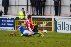 March 5 2016 - Kingfield Stadium - Woking - England - Dover Defender Sam Magri (2) takes down Woking Midfielder John Goddard (11) during the National League match between Woking & Dover Athletic.