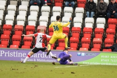 February 13 2016 - Kingfield Stadium - Woking - England - Woking Goalkeeper Jake Cole (1) claims the ball at the feet of Guiseley's James Hurst (36) during the National League match between Woking & Guiseley.