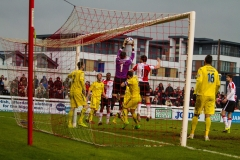 February 13 2016 - Kingfield Stadium - Woking - England - Guiseley Goalkeeper Steven Drench (1) claims a cross under pressure from Woking Striker Giuseppe Sole (10) during the National League match between Woking & Guiseley.
